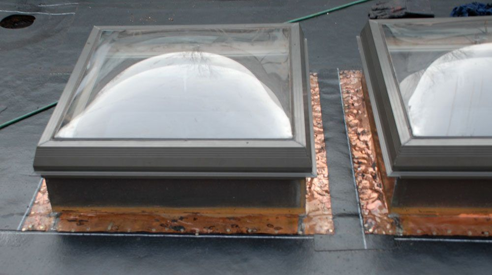 Skylight flashing on top of base roof layer