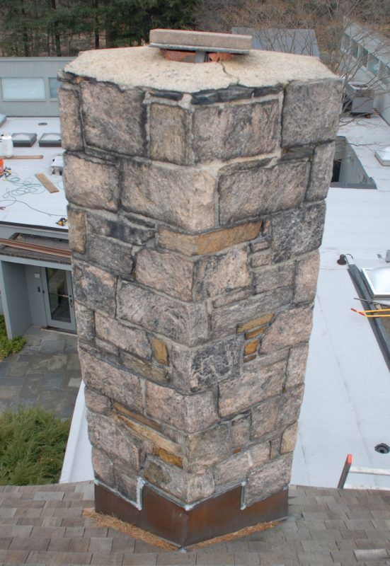 A fieldstone chimney with the crown and mortar joints cracked