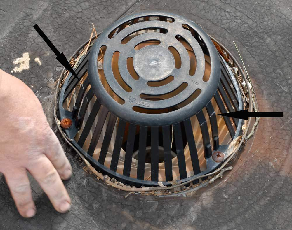 Flat Roof Drains and Strainers - Notice the cracks on this plastic strainer. Eventually, the strainer will develop more cracks, then break apart, and become ineffective.