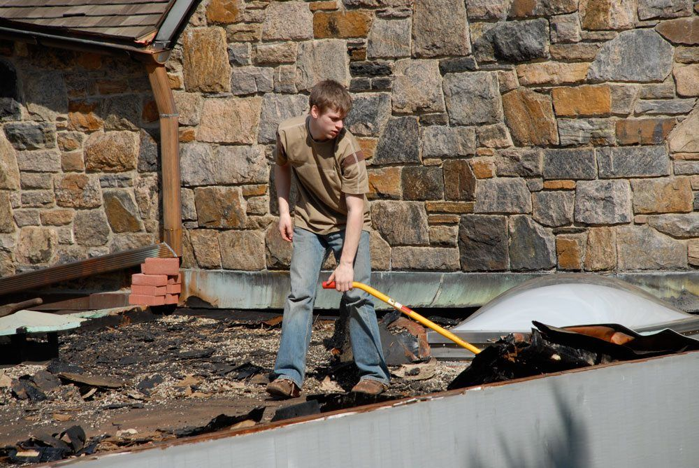Andre as a teenager helping on a roof