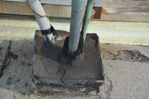 Pitch pocket filled with tar. The pipe leading through the pitch pocket will cause leaks