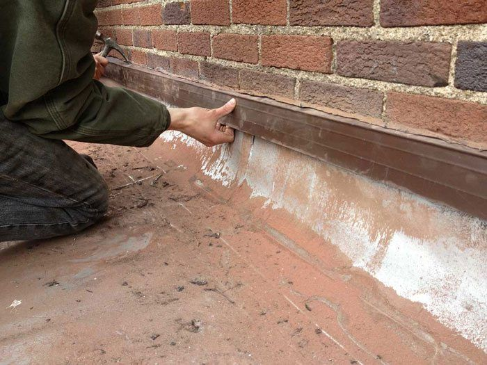 Flat Roof Repair - after cutting the grove in the brick wall, the counter flashing is installed -Flat Roof Repair - Membrane is not attached to drain and caused leaks - Philipsburg, PA